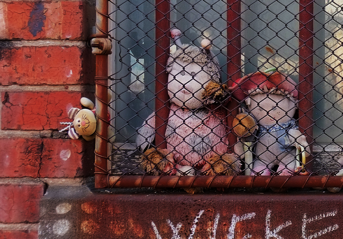 close up of three stuffies behind a rusty metal grille in front of a window.