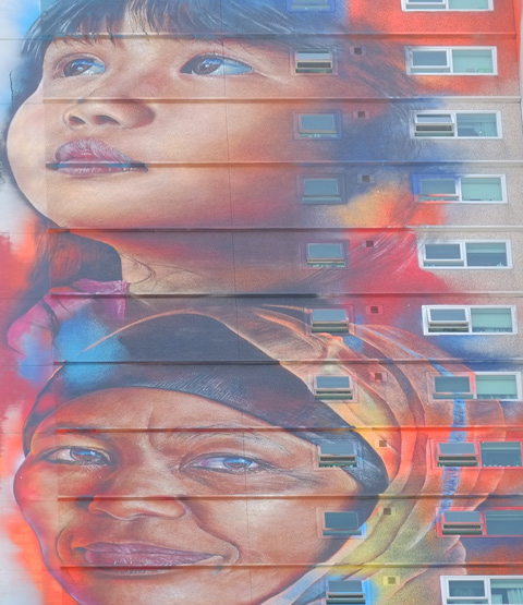 a young girl and an older woman's face in an adnate mural