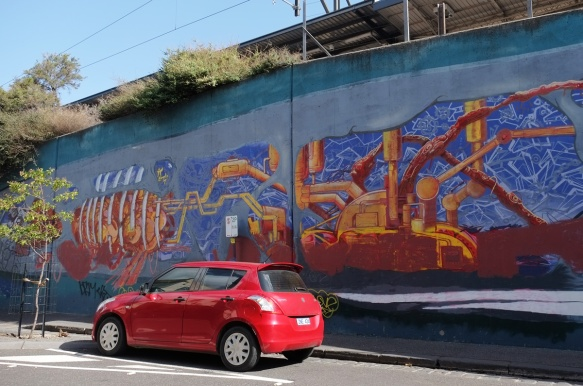 part of a whale mural, car parked in front of it, showing machinery as parts that keep the whale moving