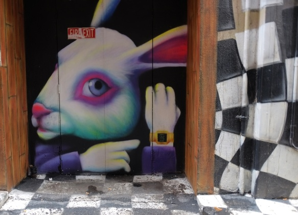 mural of a white rabbit from Alice in Wonderland, with pinkish eyes and ears, and purple jacket, and wearing a wrist watch, on a double door, surrounded by black and white checked pattern.