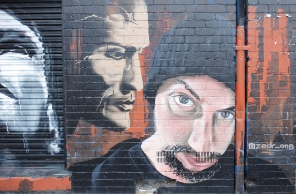 street art piece by zedr_one of two men's faces, one in profile, and the other more straight on. The second, is wearing a black toque hat and has the start of a beard and a moustache.
