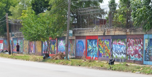 a person walks past a wall covered with many murals beside a street, South Wood Street