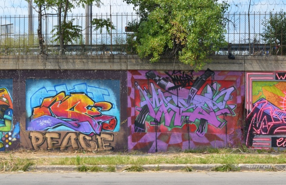 two murals on a wall beside a street, one has the word peace