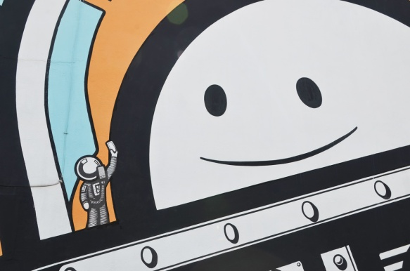 close up of big smiling astronaut face looking at a tiny astronaut, in a mural by The London Police