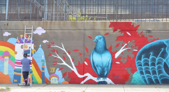 two murals, on the right is a large blue bird sitting on a white branch with a red background by fedz and on the left joey d is finishing his mural