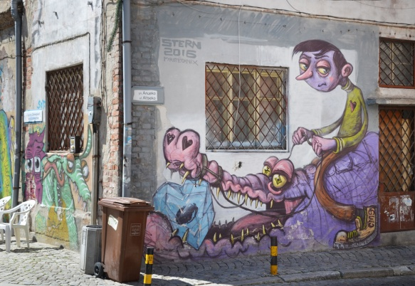 looking at the corner of a building, with murals on two sides. One side is of a man riding a purple and pink alligator or crocdile. The other side is not seen as easily and are more creatures