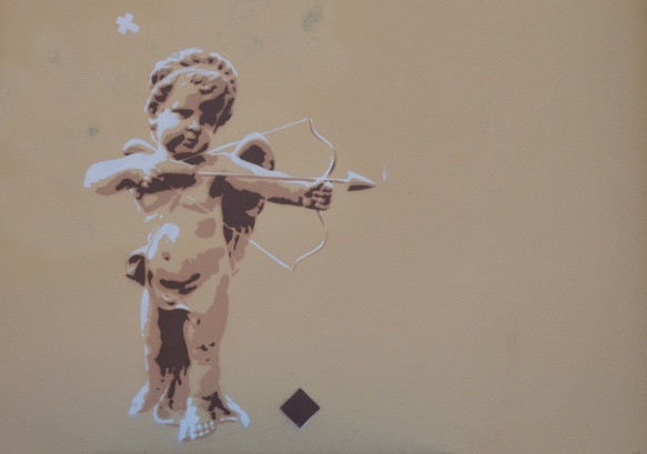 a small graffiti piece of a small chubby partially naked cupid with an arrow ready to shoot from his bow.