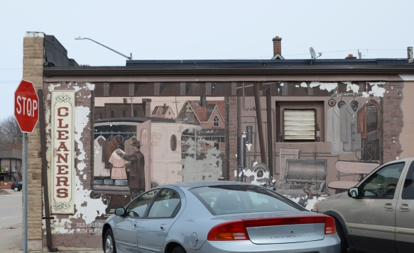 car parked in front of a mural showing the interior of an old cleaners with a man working inside hanging up a dress
