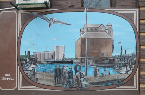 mural of an historic scene in Midland Ontario, people in fashion of the time, standing on dock looking at a boat in the water and a grain elevator