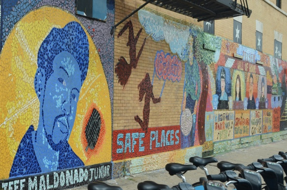 part of a mural at 18th and Paulina in Pilsen area of Chicago, by J-DEF peace project, a portrait of Jeff Maldonado Jr. for whom the project is named after, as well as a picture with the theme of create safe places away from gun violence