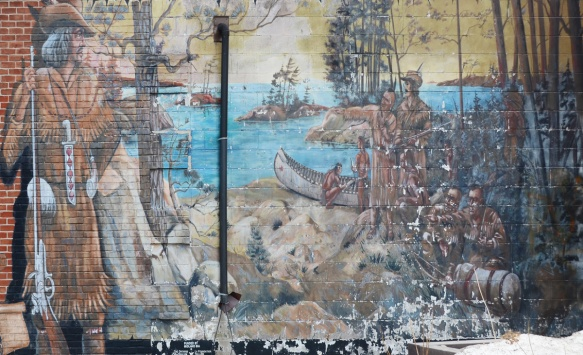 mural in bad shape (peeling paint) of a European explorer standing beside a lake scene, First Nations people and Europeans in canoes