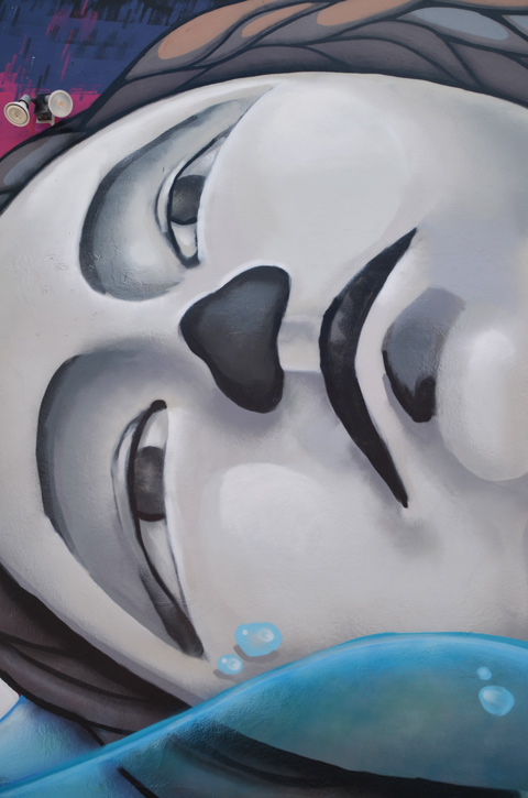 close up of woman's face in mural, in grey tones, lying on her side, width of face is height of wall, blank expression on her face