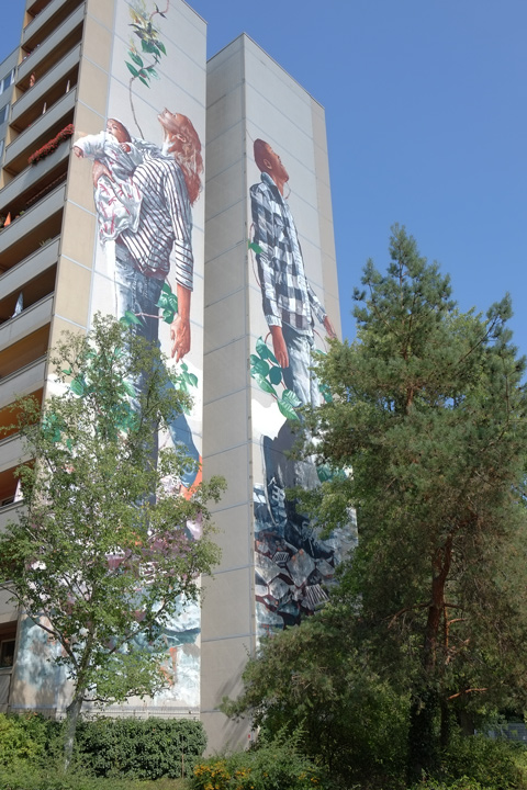 a mural by Fintan Magee, a mother and child on one side and a man, the father, on the other side, Urban Nation Tegel Art Park, large mural on side of 13 storey building,