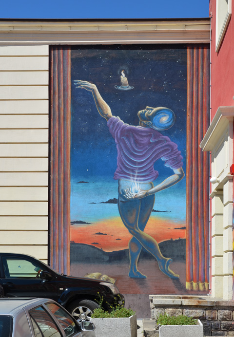 mural of a man from behind, one hand behind his back , the other hand in the air just released a candle, or is reaching for the candle