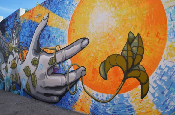 part of a mural by emo and remote, large yellow and orange sun in the middle, a hand is reaching for the sun, a vine is growing up the hand and fingers towards the sun