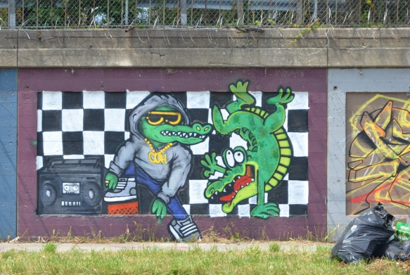 mural on a concrete wall in Pilsen, two alligators or crocodiles, one in a hoodie and one standing on one front leg and smiling