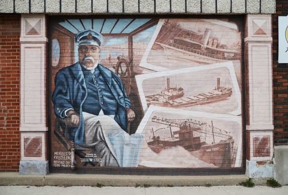 a portrait of James Playfair in a mural, long with images of some of the boats that his shipyard built