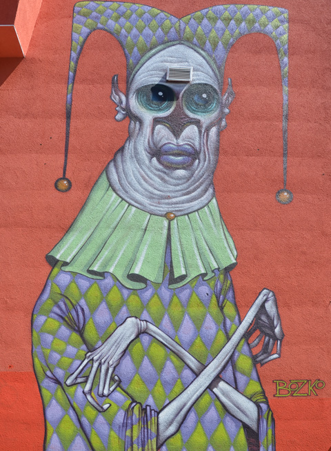 a large mural of an older man in jester outfit, with arms crossed in front of him, make up on his face