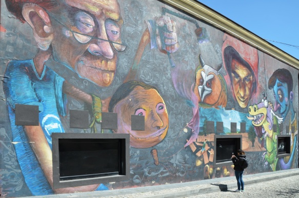 a woman is taking a photo of a large mural by Dimitar Mehandjiiski a k a stern in Plovdiv, external wall, puppets people