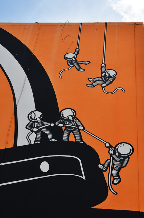 in a mural in Hollywood Florida, five small astronaut characters with ropes as they try to climb up
