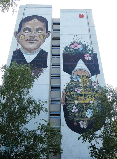 Pixel Pancho mural of two men, one with flower garden at the back of his head, Urban Nation Tegel Art Park, large mural on side of 13 storey building,