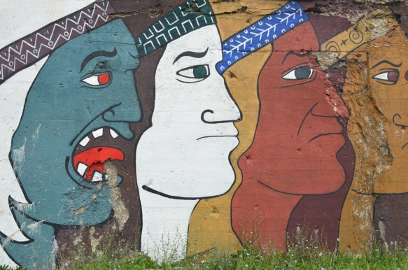 mens faces in profiles in different colours, large, about 10 feet tall, mural on a wall beside the railway tracks in Pilsen Chicago, Galeria del Barrio. One face is green and has a red tongue that is sticking out