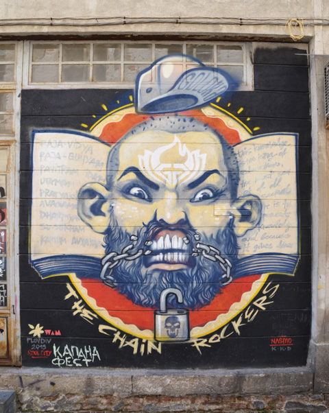 mural on a wall of the head ans shoulders of an older balding man with beard, moustache, and large white teeth. He has an angry look on his face. his collar is in Bulgarian colours, red, yellow and black. An open padlock is in his beard and a chain runs across the lower par tof his face but it lookslike he has just broken it with his teeth