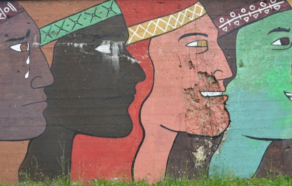 mens faces in profiles in different colours, large, about 10 feet tall, mural on a wall beside the railway tracks in Pilsen Chicago, Galeria del Barrio