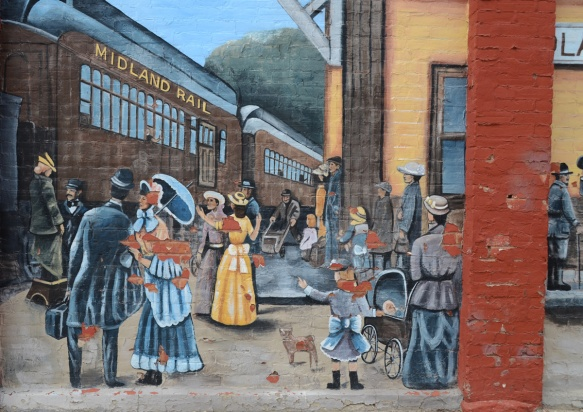 scene in a mural from Midland train station many years ago, women in long dresses and men in suits