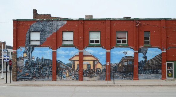 railway mural in Midland Ontario, five panels, train station, two large engines, people,