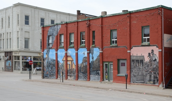 downtown midland ontario, street with reddish brick building, 2 storeys, with a large mural painted on the side