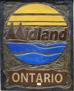 Midland ontario symbol in bronze with blue water, bronze pine trees and yellow sun