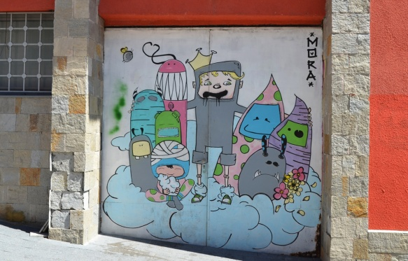 small mural of a group of cartoon-like characters standing on a blue cloud, signature is mora.