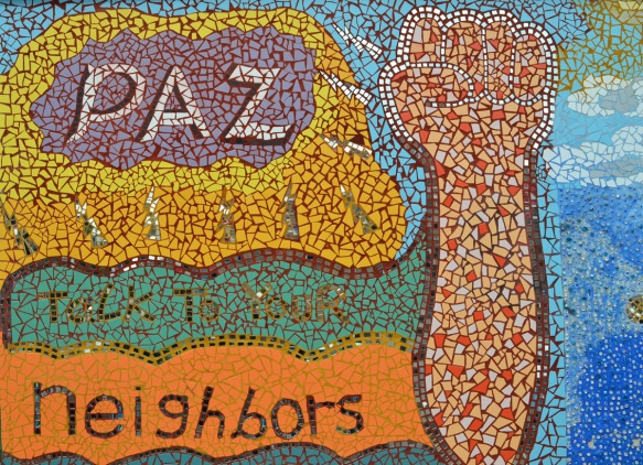 mosaic mural outside on a wall at 18th and Paulina in Pilsen area of Chicago, an arm raised with a fist along with the words paz, talk to your neighbors