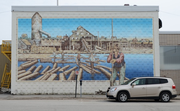 a car is parked in front of a mural of a man balancing on logs in the water, playfair mills, midland history series murals.