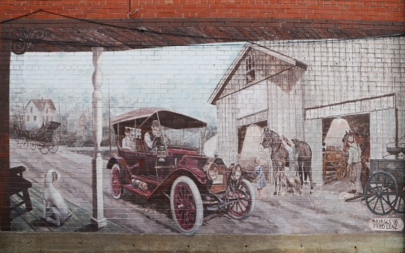 mural depicting a farm scene from a porch, with old fashioned car driving through. Barn with horse and child, also horse drawn wagon
