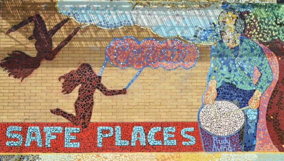 moasaic mural of tiles with words create safe places. A picture of a body outline on the ground with three red hearts, also shadows of two people with long hair on swings. A man plays a drum with the words Rudy Avina