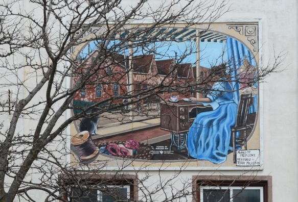 small mural behind a tree on the upper storey above a store, a woman in a long blue dress is sewing at on old fashioned sewing machine