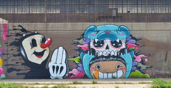 a mural with two creatures, a black cartoon cat head and shoulders, skinny arm with white gloved hand, long red nose. The other is a light blue, skull on top, smiley face with big teeth on the bottom