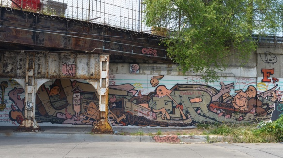 a mural that is partially under a railway bridge, metal supports for the bridge in the picture,