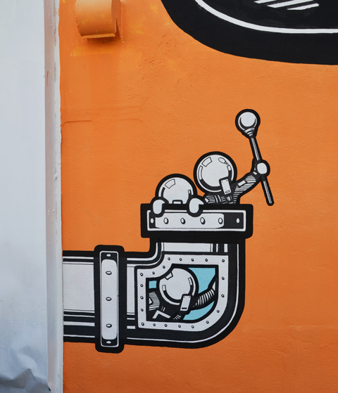 a pipe comes out of a wall, painted on a mural, small astronaut characters are coming out of the pipe