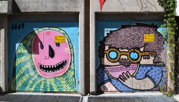 two murals side by side, one by mishka the mouse, and the other by aleksi varna. on the left is a watermelon cut open, seeds form a happy face, and the mural on the right is a person in round glasses eating a slice of watermelon