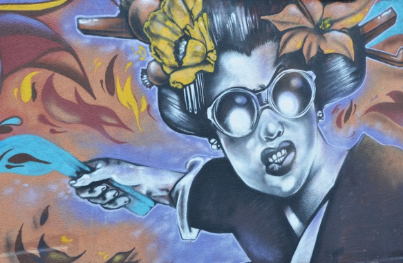 mural of a woman with large glasses and two flowers in her hair. she is holding something blue in one hand
