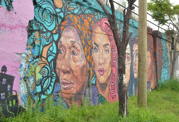part of a mural by Sam Kirk and Sandra Antongiorgi of large women's heads, some trees in the way