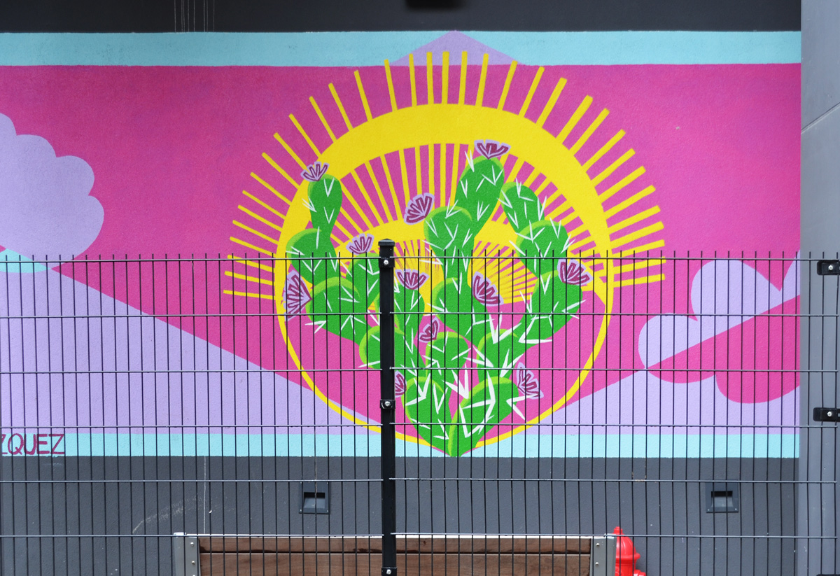 a mural behind a fence, pink, with yellow sun and green cactii