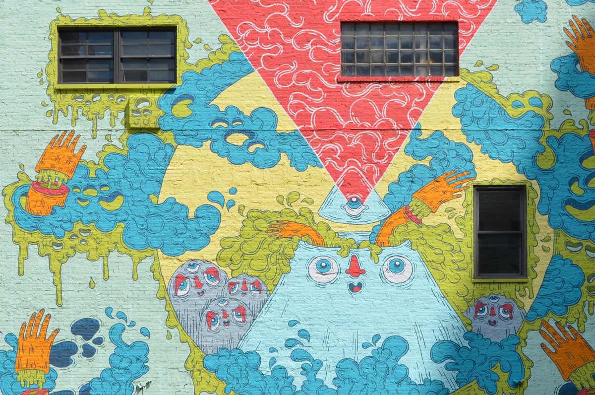 mural in pastels tones, a reddish triangle, point down, and a light blue triangle, point up, meet in the middle, face on blue one, hands and little creatures too,