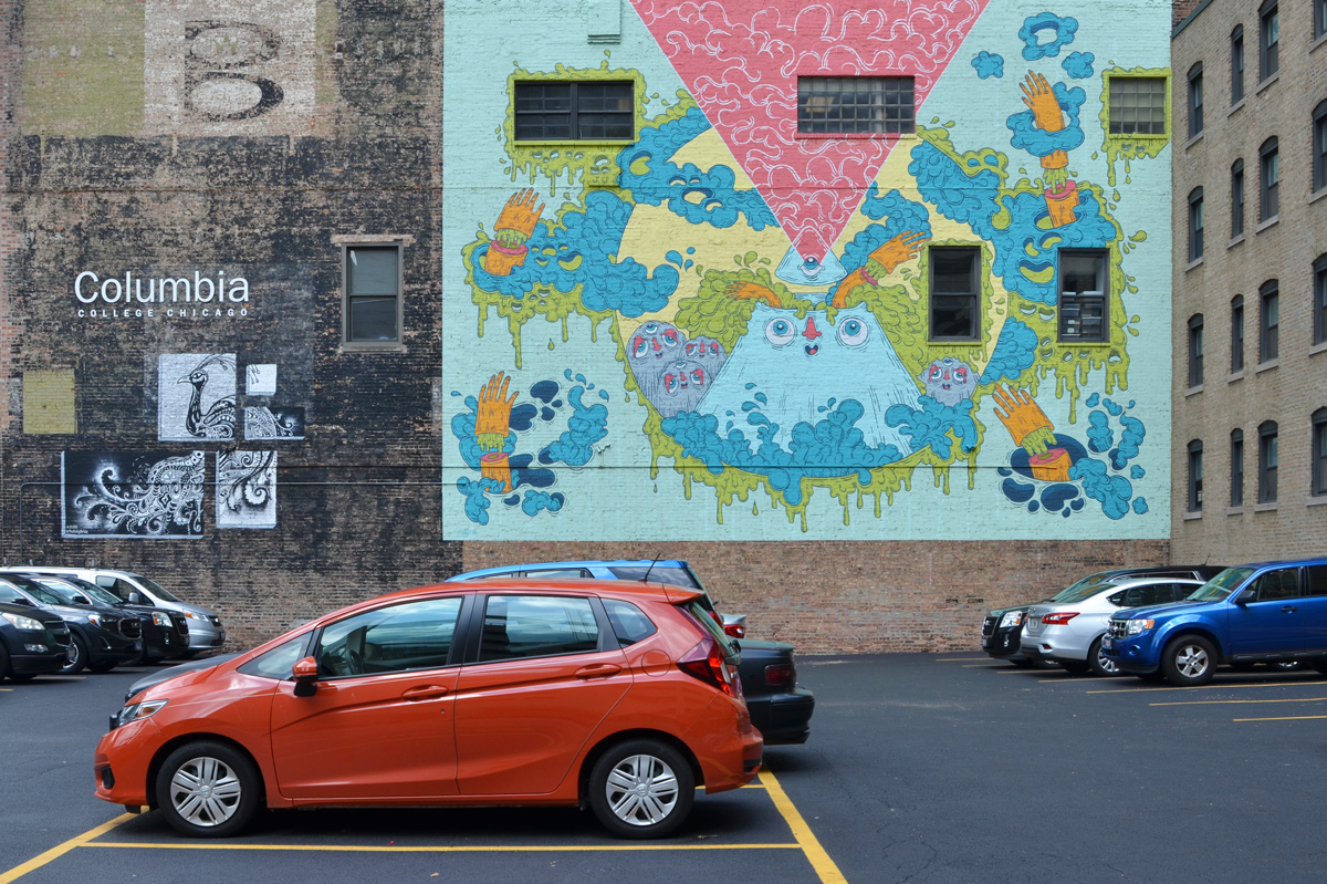 two murals on a wall on Wabash street in Chicago, on the wall Columbia college, beside a parking lot with a little bright orange car as well as other cars