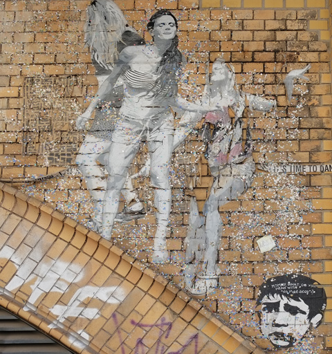 on a brick arch, a paste up in black white, life size picture of people dancing, three women, one with back showing