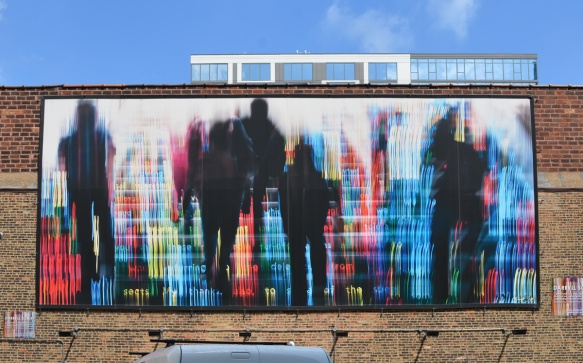 mural on a wall, black people in silhouette walking towards numbers in LED lights that look digital