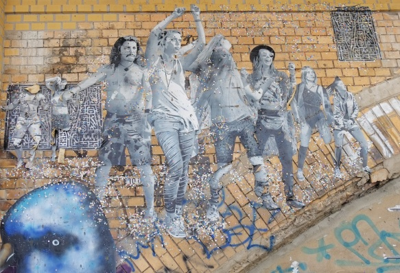 on a brick arch, a paste up in black white, life size picture of people dancing, large group both men and women, glitter too
